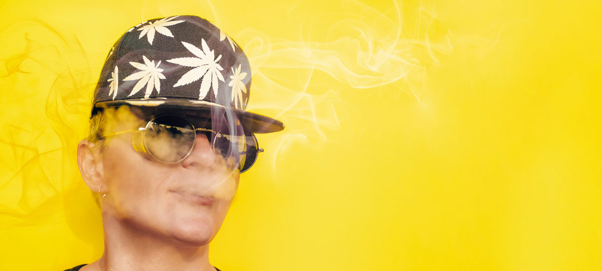 Girl in sunglasses and cap with leaves of marijuana smokes on yellow background
