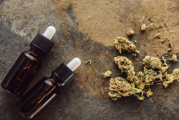 Top View of Medical Marijuana Buds Near Bottles With Hemp Oil on