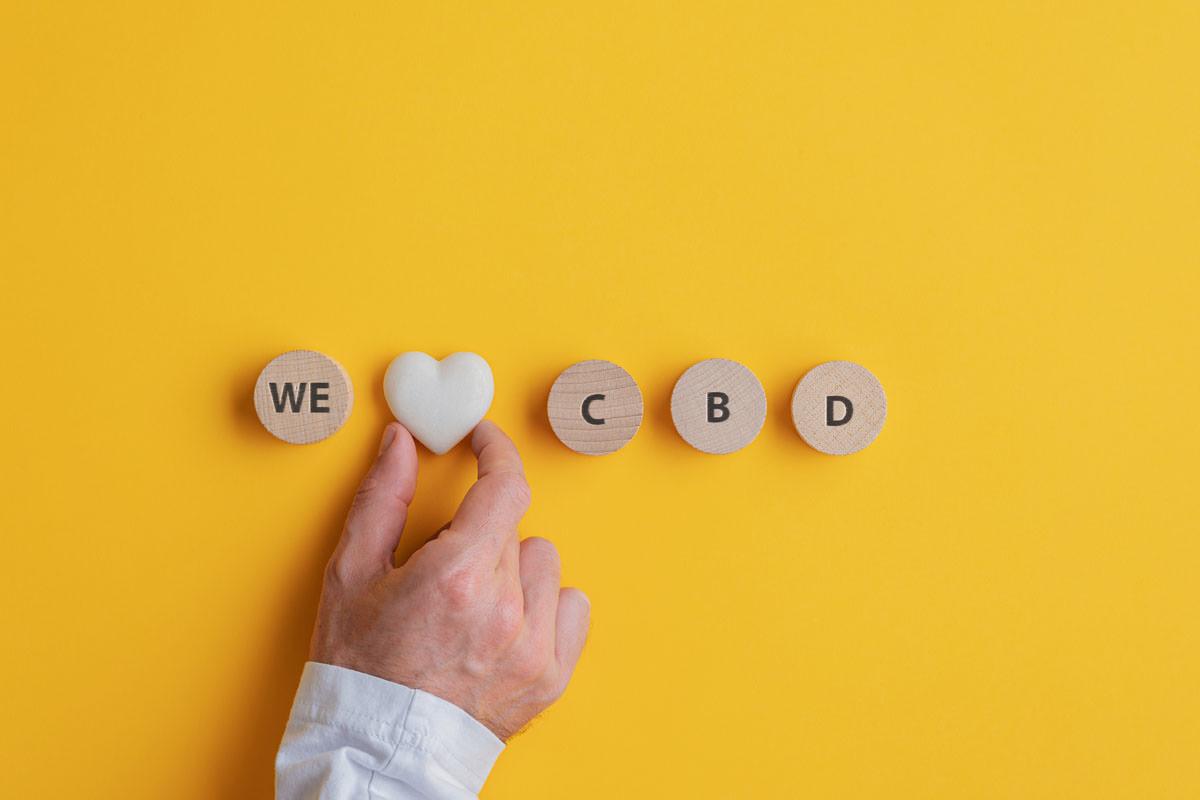 Male hand making a We love CBD sign
